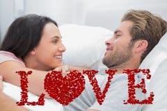 醒和看彼此的快乐的夫妇的综合图象 库存照片
