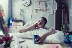 醒在办公室的疲乏的女实业家 免版税库存图片