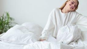 醒在她的床上的美丽的妇女在卧室,她舒展并且微笑着 股票录像