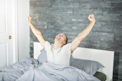 醒在床上和舒展他的胳膊的快乐的年轻人 免版税库存图片