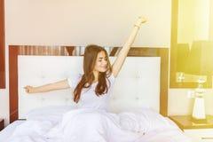 醒在床上和舒展她的胳膊的困年轻女人 E 免版税库存图片
