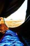 醒在日出期间 在一个帐篷外面的看法在看沙子和水的海滩在瑞典 在前景有 库存图片