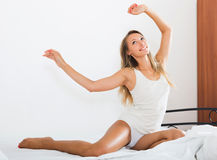 醒在白色板料的性感的妇女在床上 免版税库存照片