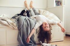 醒早晨的愉快的孩子女孩在有狗的卧室在床上 免版税库存图片