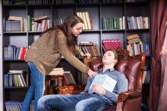 醒来一个睡觉的年轻人的女性图书管理员 免版税图库摄影