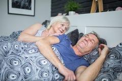 醒来她的丈夫的愉快的资深妇女在早晨 免版税库存照片