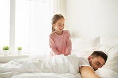 醒来她睡觉的父亲在床上的小女孩 图库摄影