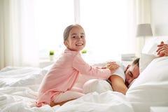 醒来她睡觉的父亲在床上的小女孩 库存图片
