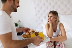 醒来有早餐的浪漫丈夫妻子在床上 免版税库存照片