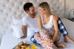 醒来有早餐的浪漫丈夫妻子在床上 库存图片