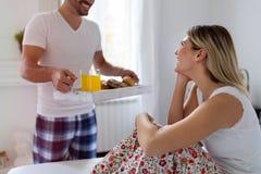 醒来有早餐的浪漫丈夫妻子在床上 库存照片
