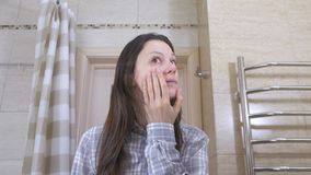 醒来的疲乏的妇女在看她的在marror和尝试的卫生间里反射按顺序投入自己 股票录像