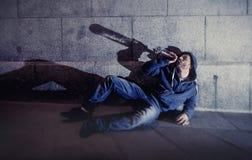 醺酒的难看的东西人坐地面街角饮用的酒精瓶 免版税库存照片