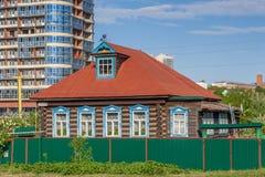采伐木屋建设中高层建筑物背景的  街道Iaroslavskaia,切博克萨雷,楚瓦什人共和国, 库存照片