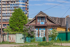采伐木屋建设中高层建筑物背景的  街道Iaroslavskaia,切博克萨雷,楚瓦什人共和国, Ru 免版税库存图片