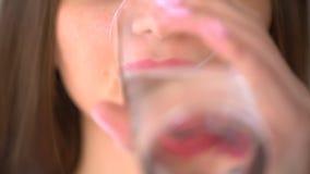 采取Ω片剂的妇女 妇女作为鱼油 采取与水的药片一个少妇打翻两三个药片入她 股票录像