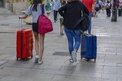 采取一个手提箱的两妇女的特写镜头图象在城市 库存图片