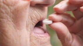 采取一个白色药片的老妇人档案缓和她的卫生问题 投入片剂的祖母在室外她的嘴 影视素材