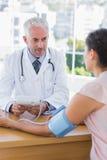 采取一名女性患者的心跳的医生 库存照片