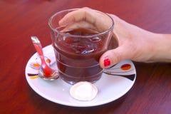 采取一块玻璃用咖啡的妇女和 免版税库存照片