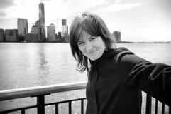 采取一张自画象(selfie)与曼哈顿摩天大楼的女孩 免版税库存照片