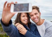 采取一愉快的selfie的爱恋的年轻夫妇户外 库存照片