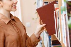 采取一本书的女孩在图书馆里 图库摄影