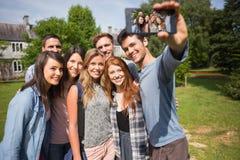 采取一selfie外面在校园里的愉快的学生 免版税图库摄影
