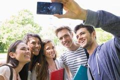 采取一selfie外面在校园里的愉快的学生 库存图片