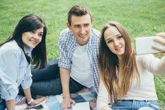 采取一selfie的小组朋友在公园在一个晴天 友谊,生活方式,休闲概念 图库摄影