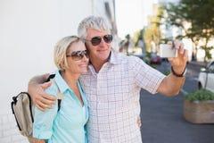 采取一selfie的愉快的旅游夫妇在城市 库存照片