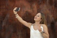 采取一selfie的美丽的女孩在公园 免版税库存照片