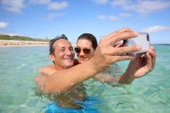 采取一selfie的年轻愉快的夫妇在海 免版税库存图片