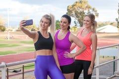 采取与一个手机的三位女性一selfie 免版税库存照片