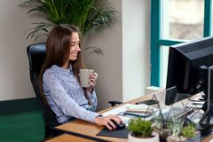采取与一个杯子的办公室工作者一个咖啡休息浓咖啡在她的手上 库存照片