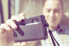 采取与一台老影片照相机的年轻人一selfie,被过滤 库存图片