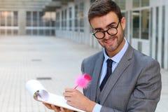 采取与一支逗人喜爱的桃红色笔的惊奇的华腴商人笔记 库存图片