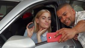 采取与他们新的汽车的愉快的爱恋的夫妇selfies 股票视频