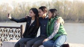 采取与他们的智能手机的三个美丽的亚裔少年一滑稽的selfie 股票视频