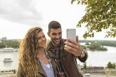 采取与他可爱的女朋友的英俊的年轻人selfie 库存图片