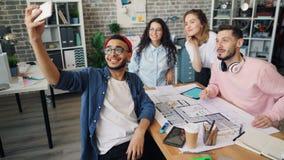 采取与创造性的队的企业主selfie与智能手机照相机在办公室 影视素材