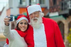 采取与圣诞老人的妇女一selfie 免版税图库摄影