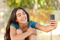 采取与她巧妙的电话的愉快的青少年的女孩一张selfie画象 免版税库存图片