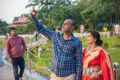 采取与她的妻子的年轻人selfie在庭院里 免版税库存图片