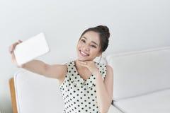 采取与她的手机的愉快的年轻女人selfie,当坐在客厅时 免版税库存图片