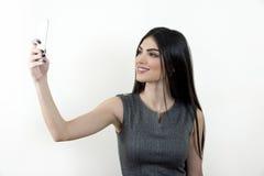 采取与她的智能手机的女商人selfie 库存图片