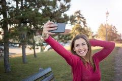 采取与她的电话的美丽的女孩一selfie在公园 库存照片
