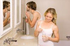 采取与她的男朋友的白肤金发的妇女一个药片刷他的牙 免版税库存照片