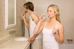 采取与她的男朋友的白肤金发的妇女一个药片刷他的牙 免版税图库摄影