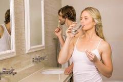 采取与她的男朋友的白肤金发的妇女一个药片刷他的牙 库存图片